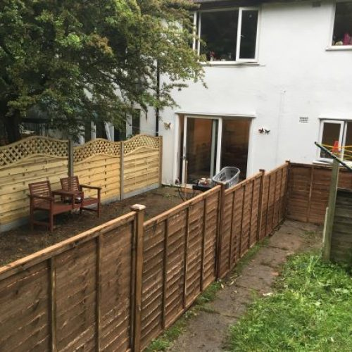 To the left of picture Nottingham fence panels with trellised top concrete post and 6 in concrete gravel boards right-hand side is Waney lap also known as Kent lap pane